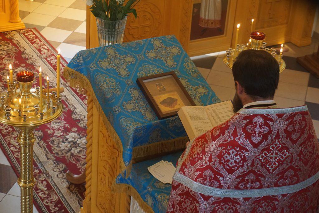 Священник читает молитвы перед иконой